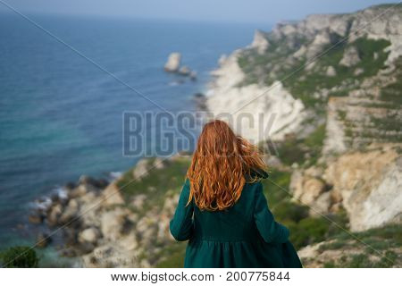 beautiful young woman on the precipice of a mountain near the sea.