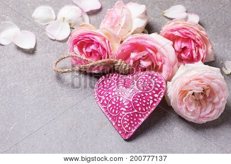 Fresh pink roses and decorative pink heart on grey slate background. Selective focus. Place for text. Shabby chic.