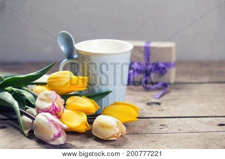 Bright yellow and white spring tulips and blue cup on wooden background. Selective focus. Place for text.