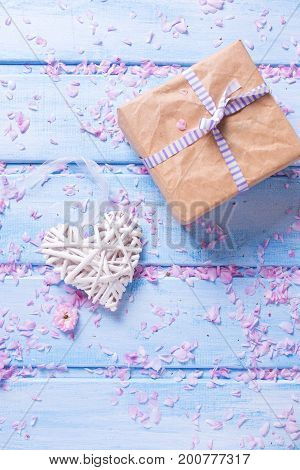 White decorative heart and box with present on blue wooden planks. Selective focus is on heart. Place for text. Vertical image.