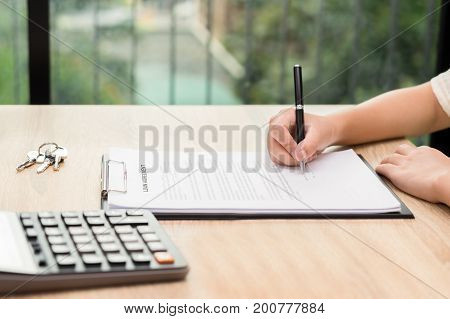 Woman signing car agreement contract with key and calculator on wooden desk