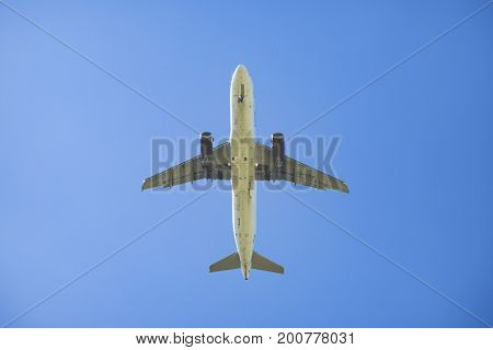 View from below of an airplane with blue sky background