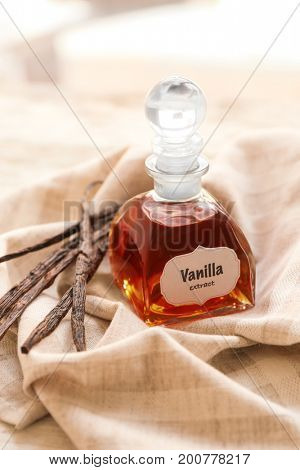 Bottle with aromatic extract and dry vanilla beans on napkin