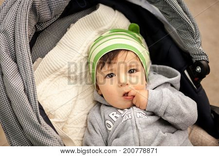 Gorgeous Baby in carriage outdoor taking a walk. Beautiful baby boy