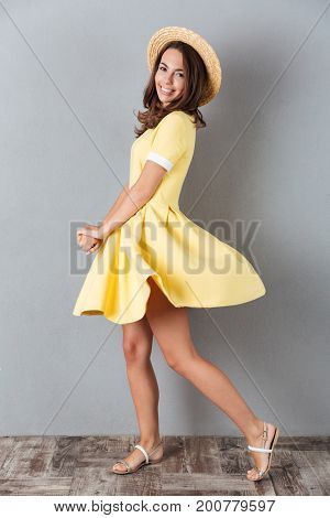 Full length of happy young girl in hat and dress spinning around and looking at camera isolated over gray background