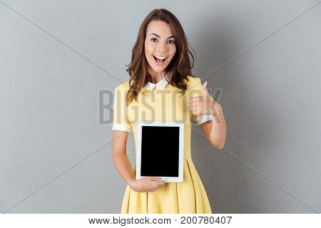 Image of cheerful young caucasian lady showing display of tablet computer. Looking camera showing thumbs up.