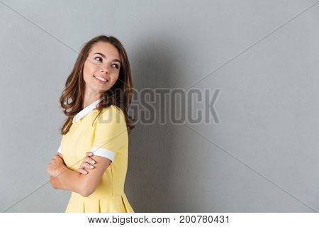 Happy smiling girl with arms folded looking away at copy space isolated over gray background