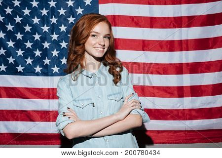 Picture of happy redhead young lady standing over USA flag. Looking camera.