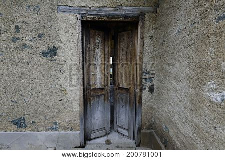 Weathered wooden door with a metallic rusty lock textured with white paint chipped and peeling