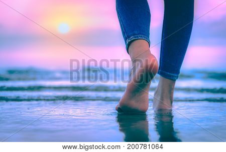 Close-up of female foot Woman's feet walking to the sea in sunset colorful sky. Vacation traveling and freedom concept.- Vintage tone.