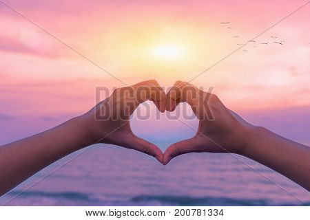 Female hands in the form of heart against sunlight in sunset sky, twilight time. Hands in shape of love heart, Love concept.