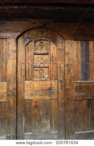 Old weathered carved traditional Italian door of building in Courmayeur Northern Italy.