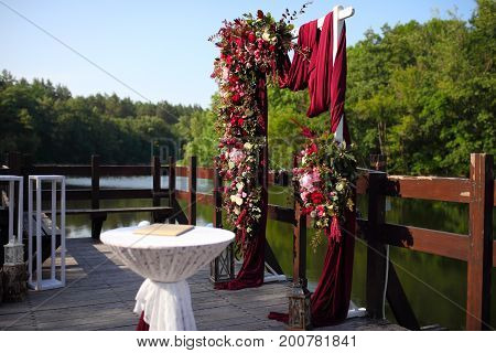 Arch For The Wedding Ceremony. Arch, Decorated With Beautiful Fresh Flowers And Cloth. Bordeaux Colo