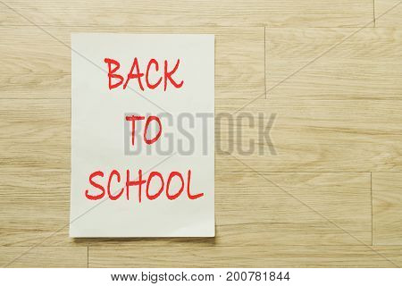 Writing paper with back to school text over wooden background.