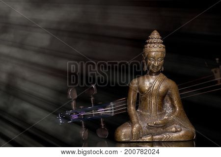 Bronze buddha meditating with comtemporary violin in divine beam of light. Traditional classical music therapy image representing spiritual and sacred music..