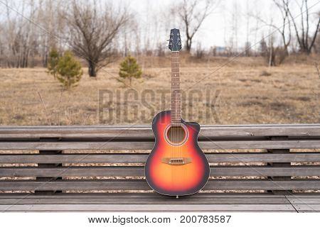 Acoustic guitar on a bench outdoors in the park on a cloudy spring day.