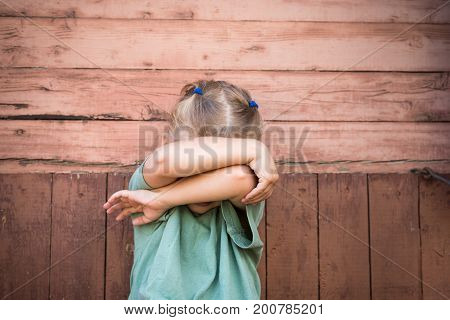 Little 3-year-old girl covering her face with arms as if she is playing hide-and-seek or is being afraid of something.