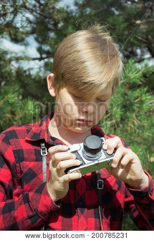 Teen is holding study an old and vintage photo-camera in red checkered shirt. Outdoors.