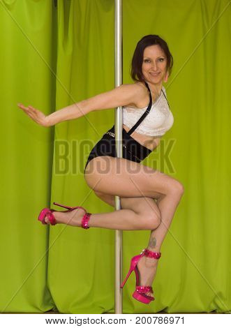 Exotic poledancer doing trick staing on hands near pole