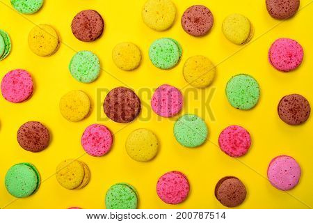 Colorful pastry macarons on a yellow background close up