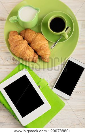 Coffee with milk croissants smartphone e-book and a notepad. Selective focus.