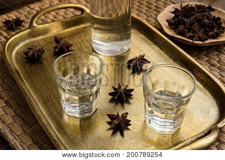 Glasses of traditional drink Ouzo or Raki on bronze dish with anise star seeds