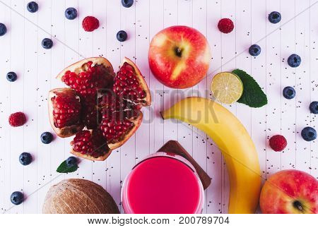 Detox diet concept: pink smoothie with fruits and berries on white wooden table. Superfoods and healthy lifestyle.