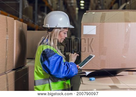 Female warehouse worker using tablet pc near boxes with merchandise
