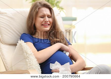 Emotional pregnant woman sitting in arm chair and crying. Pregnancy hormones concept