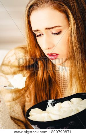 Young depressed woman is eating big bowl of ice creams to comfor