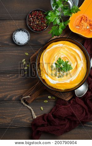 Pumpkin cream soup with cream and pumpkin seeds on wooden background, top view