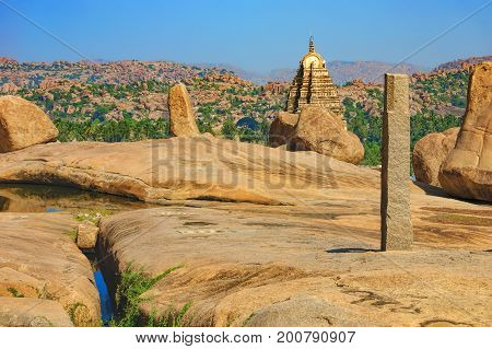 View of ancient ruins on Hemakuta hill in Hampi, Karnataka, India. Landscape with unique mountain formation with amazing stones tropical nature and Virupaksha Temple on the horizon.