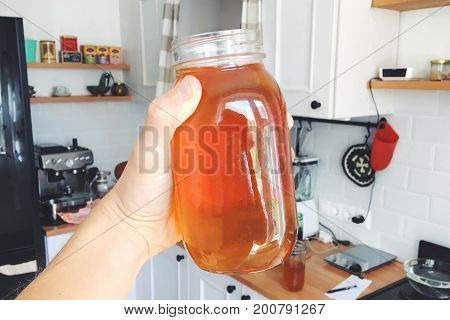 Hand Holding Jar of Homemade Organic Kombucha at House Kitchen. Healthy Hipster Vegan Lemonade Drink.