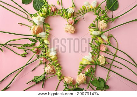 Composition of beautiful roses and freesia flowers on pink background