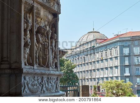 Naples Italy - August 7 2017. Rientro vittorioso di Alfonso I detail of the 1470 triumphal arch of Castel Nuovo Maschio Angioino with Galleria Umberto I dome in background. Naples. Campania Italy.