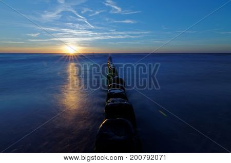 Sunset over the sea. Breakwater on the smooth surface of the sea.