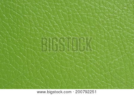 A bright green artificial leather background texture close-up