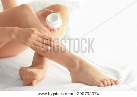 Beautiful young woman applying cream onto legs while sitting on bed at home. Epilation concept
