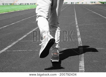Sporty young man running at stadium
