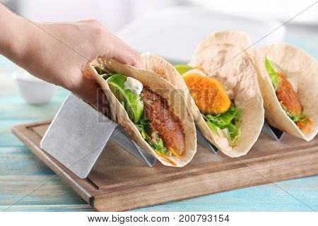 Hand taking delicious fish tacos from stand on table