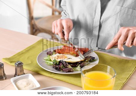 Woman eating fried egg, sausages and mix salad at table
