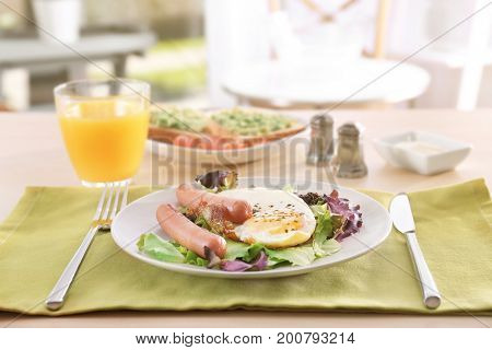 Plate with homemade fried egg, sausages and mix salad on table