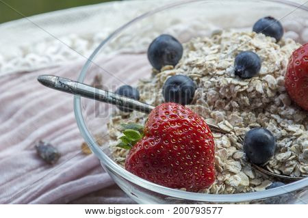One glass bowl with old teaspoon, cereals, strawberries and blueberries on the pink tissue