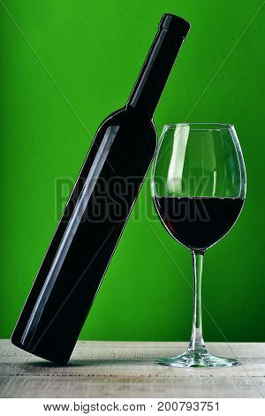 Glass Of Wine Standing On Wooden Surface And Holds Bottle