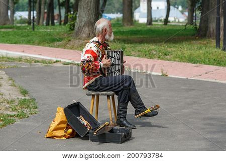 SUZDAL/ RUSSIA - AUGUST 19, 2017. An elderly man in the Russian national costume playing the accordion in Suzdal, Vladimir region, Russia.