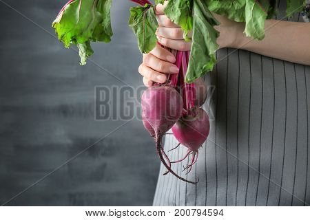 Woman holding young beets on grey background