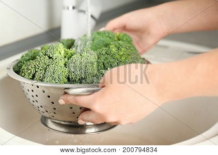 Woman's hands holding broccoli sprouts under running water in kitchen sink