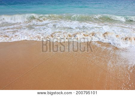 Beach shore with waves crushing on sand. Vivid summer season image, tropical vacation background. Sunny bright day light with clear blue water and empty copy space. Travel tourism relax holiday concept