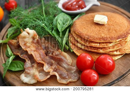 Tasty breakfast with pancakes, bacon and vegetables on wooden board, close up
