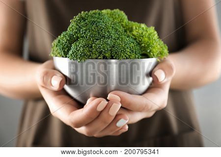 Hands holding metal bowl with fresh green broccoli
